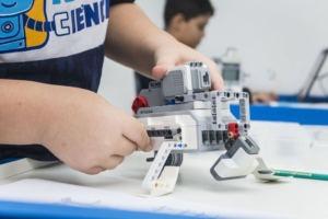 Aluno segura robô feito de Lego durante aula da Robô Ciência.