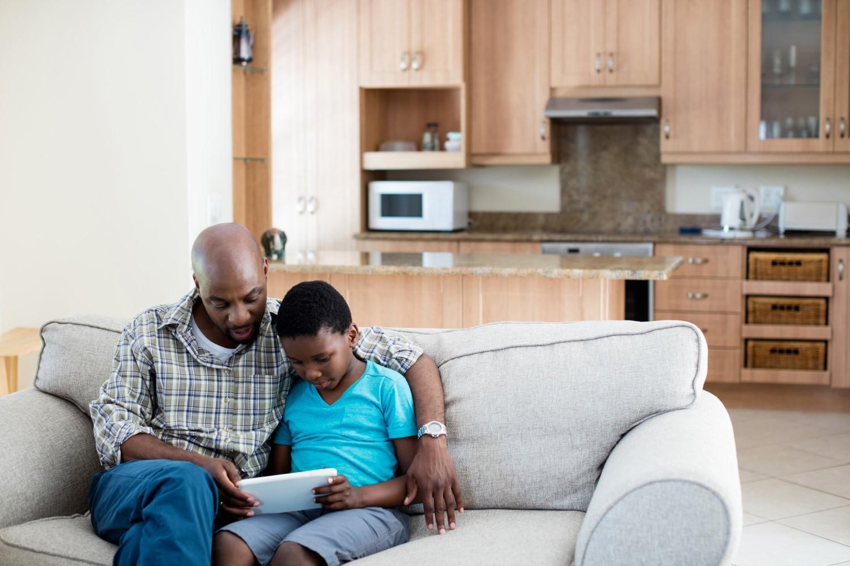 Um homem adulto e um menino pretos estão sentados em um sofá lendo em um tablet branco. O pai usa uma camiseta quadriculada, o menino uma camiseta azul. No fundo, uma sala.