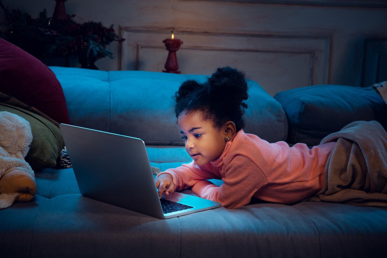Foto colorida de uma menina negra com cabelo cacheado. Ela usa um laptop e está deitada em um sofá.