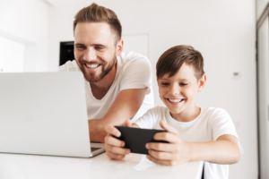 Um homem adulto e um menino brancos estão sentados. O pai usa um laptop, o filho usa um smartphone. Ambos usam camisetas brancas.