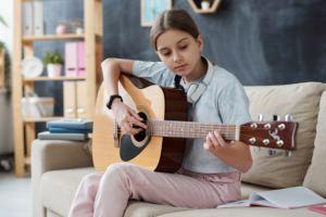 Uma menina branca toca violão sentada em um sofá. Ela usa uma blusa azul e calça rosa. No fundo, uma estante com objetos.